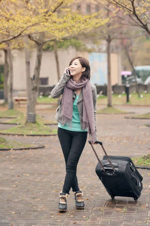 Traveling Asian lady talking on cellphone and holding a luggage in city, Taipei, Taiwan. photo
