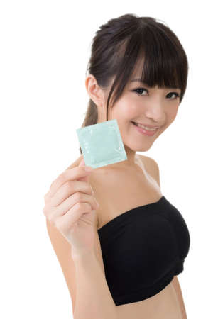 Young pretty asian woman with a condom in her hand. Isolated on the white background. photo