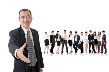 Jistý podnikatel potřást rukou s vámi a stojí v přední části svého týmu na studio bílém pozadí.