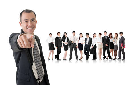 Smiling businessman of Asian point at you and standing in front of his team on studio white background. photo