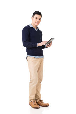 Handsome young Asian man using pad, full length portrait isolated on white background.
