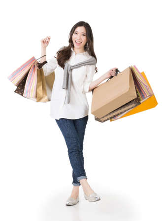 Smiling happy Asian woman shopping and holding bags, full length portrait isolated on white background. Stock Photo