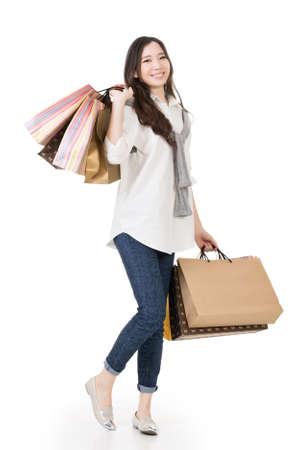 ショッピング バッグ、白い背景で隔離完全な長さの肖像画を保持している幸せのアジア女性の笑みを浮かべてください。