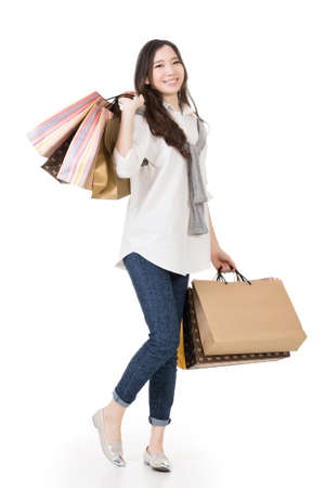 Smiling happy Asian woman shopping and holding bags, full length portrait isolated on white background. 版權商用圖片