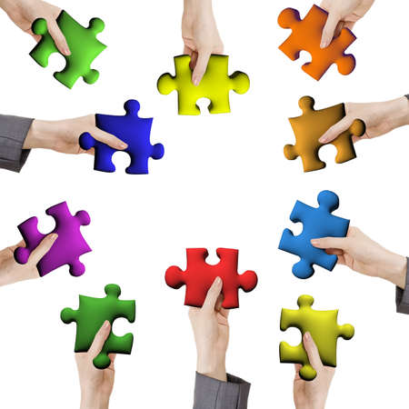 Concept of help or working together, hands holding various color puzzle pieces on white background. photo
