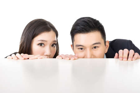 Asian business man and woman hide under the table and looking somewhere. Stock Photo