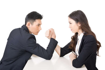 female wrestling: Arm wrestling challenge between a young business man and woman, closeup portrait on white background.