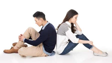nešťastný: Mladí Asijské pár sedět na zemi zády k sobě s nešťastným výrazem na studio bílém pozadí.