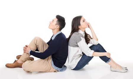 Young Asian couple sit on ground back to back and raise their head thinking on studio white background. Stock Photo