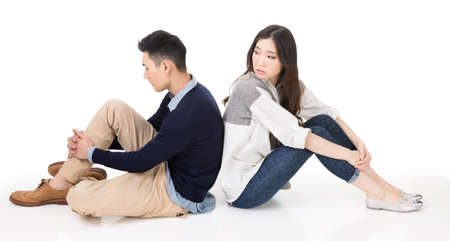 turn back: Young Asian couple sit on ground back to back and one turn back to care on studio white background.