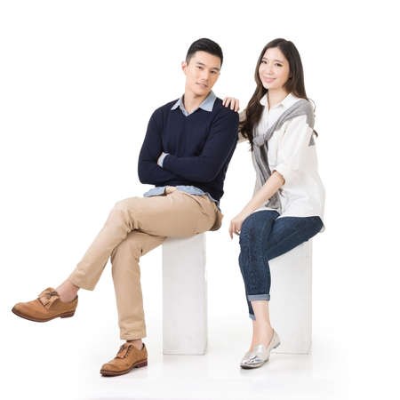 Portrait of young Asian couple sit on white box, full length portrait isolated on studio white background.