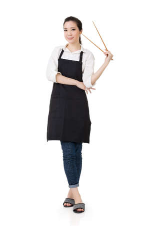 asian chef: Young Asian housewife hold a chopsticks in apron, full portrait isolated on white background. Stock Photo