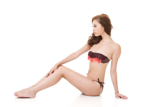Sexy bikini woman of Asian sit on ground, full length portrait isolated on white background.