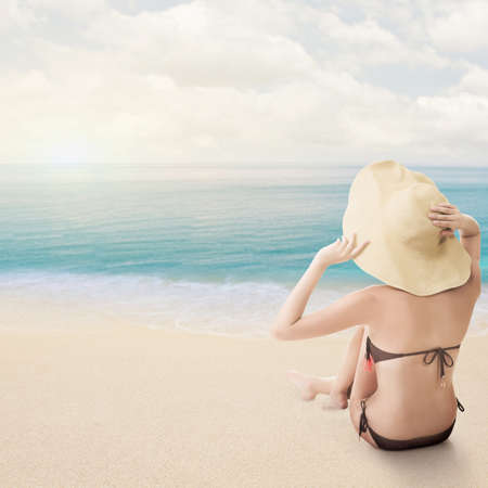 Attractive bikini beauty of Asian sit on beach and looking far away, rear view with copyspace. photo