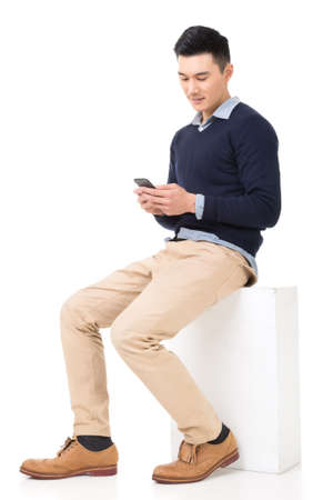 Handsome Asian guy sit and read message on his smartphone, full length portrait isolated on white background. photo