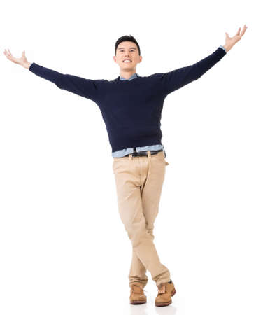Excited Asian young man, full length portrait. Reklamní fotografie