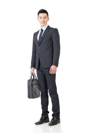 Confident young business man with briefcase, full length portrait isolated on white background. Stock Photo
