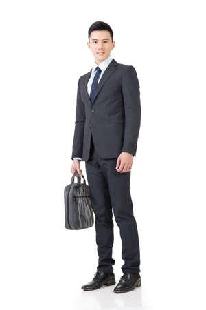 Zekere jonge zakenman met aktetas, volledige lengte portret geïsoleerd op een witte achtergrond.