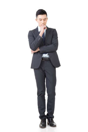 Confused young business man standing and thinking, full length portrait isolated on white background.