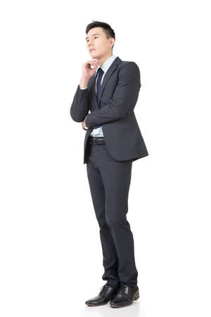 consider: Confused young business man standing and thinking, full length portrait isolated on white background.