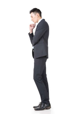 business concern: Confused young business man standing and thinking, full length portrait isolated on white background.