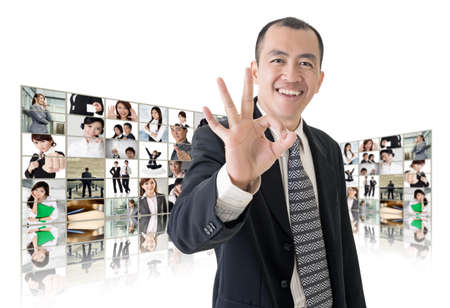 Asian business man or boss standing in front of TV screen wall showing pictures of business concept. Stock Photo - 26654676