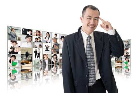 Asian business man or boss standing in front of TV screen wall showing pictures of business concept. Stock Photo - 26654704