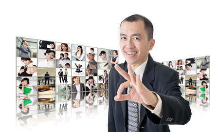 Asian business man or boss standing in front of tV screen wall showing pictures of business concept. Stock Photo - 26654712