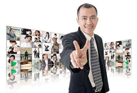 Asian business man or boss standing in front of TV screen wall showing pictures of business concept. photo