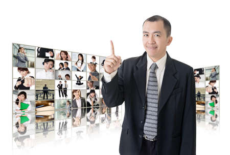 Asian business man or boss standing in front of tV screen wall showing pictures of business concept. Stock Photo - 26654649