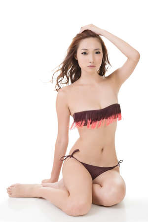 Sexy Asian bikini woman sit on studio white ground. photo