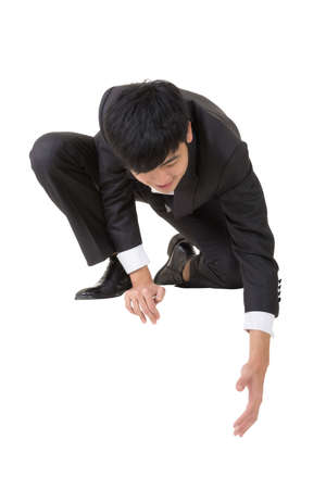 Asian businessman sit and bend down to help somebody, full length portrait isolated on white. photo