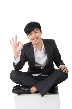 man face close up: Asian businessman sit and give you an okay sign, full length portrait isolated on white.