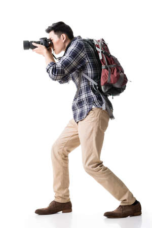staring at the camera man: Asian young male backpacker take a picture, full length portrait isolated on white.