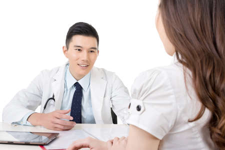 Asian doctor man talking to a woman in hospital office. photo