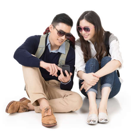 travellers: Asian young couple traveling and sitting on ground and using mobile phone, full length portrait on white background.