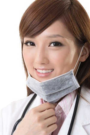 Asian doctor woman take off the surgical mask and smile at you, closeup portrait. photo