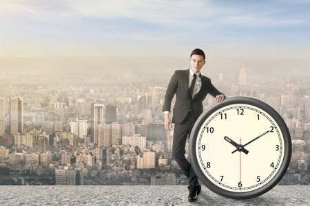 manage: Asian businessman standing with a clock, concept of time manage or plan.