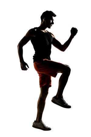 Silhouette of young Asian athlete running, full length portrait isolated on white  photo