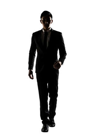 Confident businessman walking toward you, silhouette portrait isolated on white. Stock Photo
