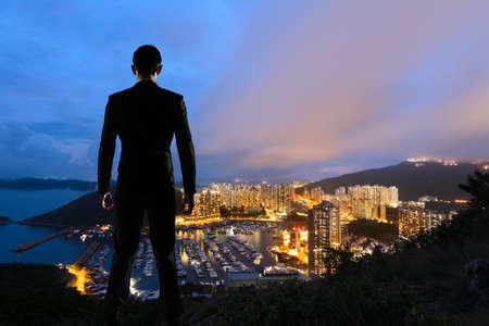 Asian businessman standing in the hill and looking at the skyscrapers and harbor in Aberdeen, Hong Kong, Asia. photo
