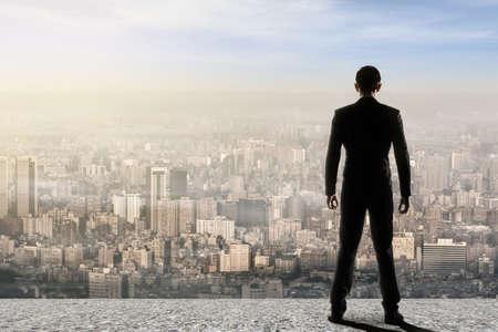 Concept van het succes met een zakenman die zich op het dak en vooruit te kijken naar de mogelijkheden. Achteraanzicht.