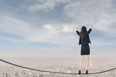 Risk Free: Asian business woman standing on rope and feel exciting, concept about adventure, risk, success, win etc.