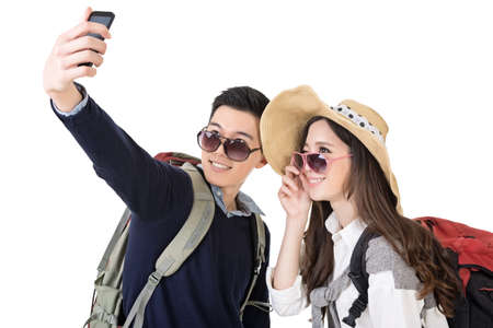 Asian young traveling couple selfie, full length portrait isolated on white background. photo