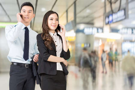 Asian business man and woman talking on cellphone in the station of Hong Kong, Asia. photo