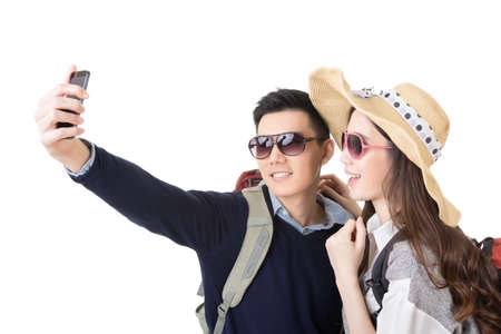 travelers: Asian couple travel and take a selfie on white background.