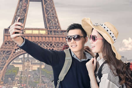 Asian couple travel and take a selfie at Eiffel Tower, Paris, France. photo
