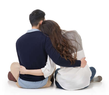 rear: Asian couple sit on ground and hug each other, rear view on white background.