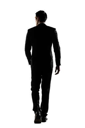 Silhouet van Aziatische zaken man lopen met vertrouwen, volledige lengte portret op wit wordt geïsoleerd. Achteraanzicht.