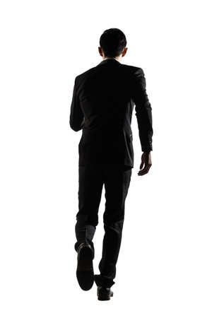 Silhouette of Asian business man running, full length portrait isolated on white. Rear view. photo